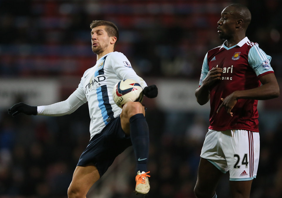 Photo - West Ham's Carlton Cole, right, looks on as Manchester City's Matija Nastasic controls the ball during the second leg of the English League Cup semifinal soccer match between West Ham United and Manchester City in London, Tuesday, Jan. 21, 2014. (AP Photo/Alastair Grant)
