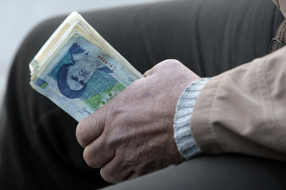 Photo -   FILE- In this Thursday, Jan. 26, 2012 file photo, an Iranian street money changer holds Iranian banknotes with a portrait of late revolutionary founder Ayatollah Khomeini, in the main old Bazaar of Tehran, Iran. President Mahmoud Ahmadinejad blamed the steep drop in Iran's currency Tuesday to