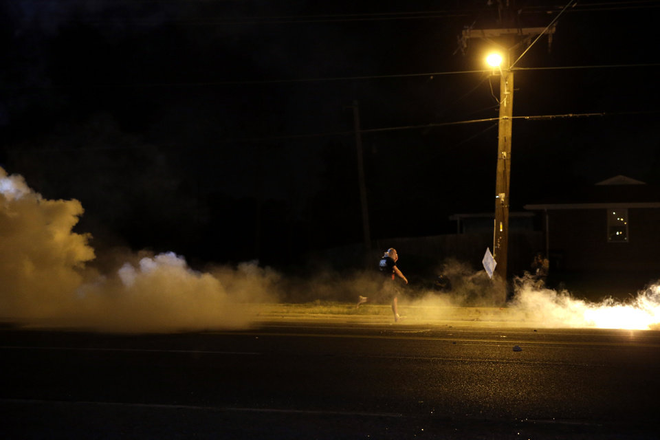 Photo - A protester runs through smoke deployed by police Wednesday, Aug. 13, 2014, in Ferguson, Mo. Protests in the St. Louis suburb rocked by racial unrest since a white police officer shot an unarmed black teenager to death turned violent Wednesday night, with people lobbing Molotov cocktails at police who responded with smoke bombs and tear gas to disperse the crowd. (AP Photo/Jeff Roberson)