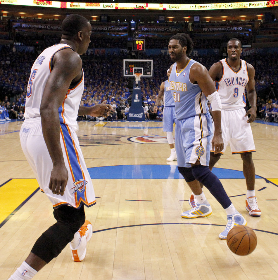 Denver\'s Nene (31) reacts between Oklahoma City\'s Kendrick Perkins (5) and Serge Ibaka (9) during the NBA basketball game between the Denver Nuggets and the Oklahoma City Thunder in the first round of the NBA playoffs at the Oklahoma City Arena, Sunday, April 17, 2011. Photo by Bryan Terry, The Oklahoman