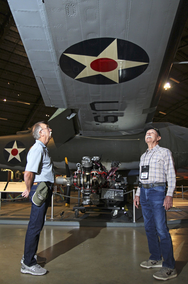 Photo - In this Sept. 27, 2013 photo former B-25 crewman George Williams, right, and Mike Williams look at the wing of a B-25 bomber during a reunion of the 57th Bomb Wing in front of a B-25 bomber in the U.S. Air Force Museum at Wright Patterson Air Force base in Dayton, Ohio. George Williams rememberes the tension of his first mission, his hand ready at the tag that would release him to bail out if necessary. It went without incident, and upon their return to base, a flight surgeon measured out two ounces of whiskey for each crewman.