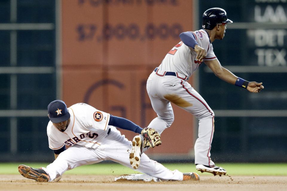 Photo - Houston Astros' Marwin Gonzalez, left, vainly tries to tag Atlanta Braves' B.J. Upton (2) who steals second base and then goes on to third on a throwing error by Astros catcher Jason Castro in the first inning of a baseball game Thursday, June 26, 2014, in Houston. (AP Photo/Pat Sullivan)