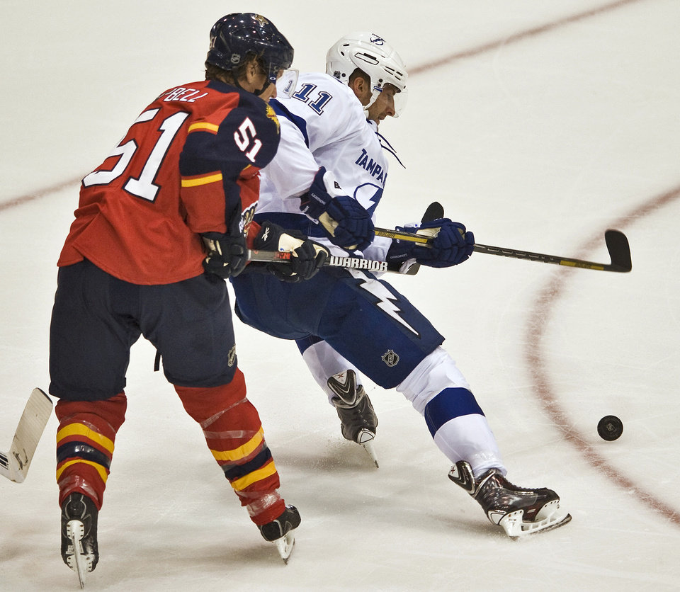 Photo - Florida Panthers' Brian Campbell (51) defends Tampa Bay Lightning forward Tom Pyatt (11) during the first period of an NHL preseason hockey game Thursday, Sept. 26, 2013 in Estero, Fla. (AP Photo/Steve Nesius)
