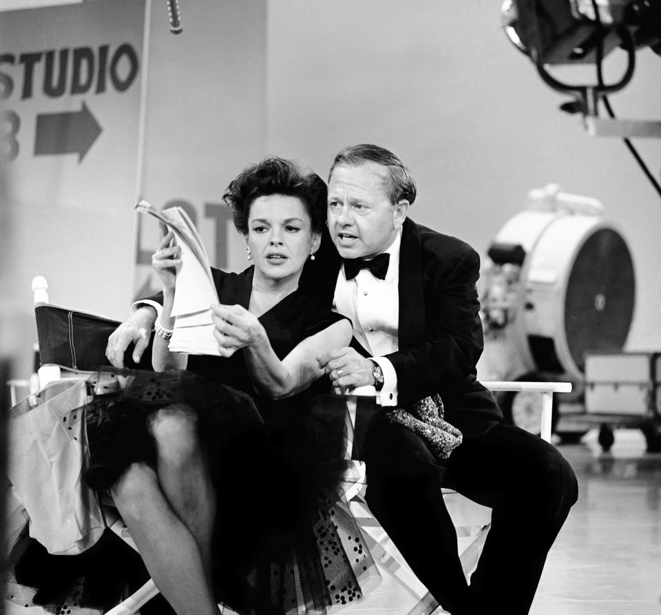 Photo - FILE - In this June 26, 1963, file photo, Judy Garland and Mickey Rooney put their heads together over a television script for their first onstage reunion in 18 years, for the taping of the first of 32 variety shows which Garland will do for CBS next season. Rooney, a Hollywood legend whose career spanned more than 80 years, has died. He was 93. Los Angeles Police Commander Andrew Smith said that Rooney was with his family when he died Sunday, April 6, 2014, at his North Hollywood home. (AP Photo/File)