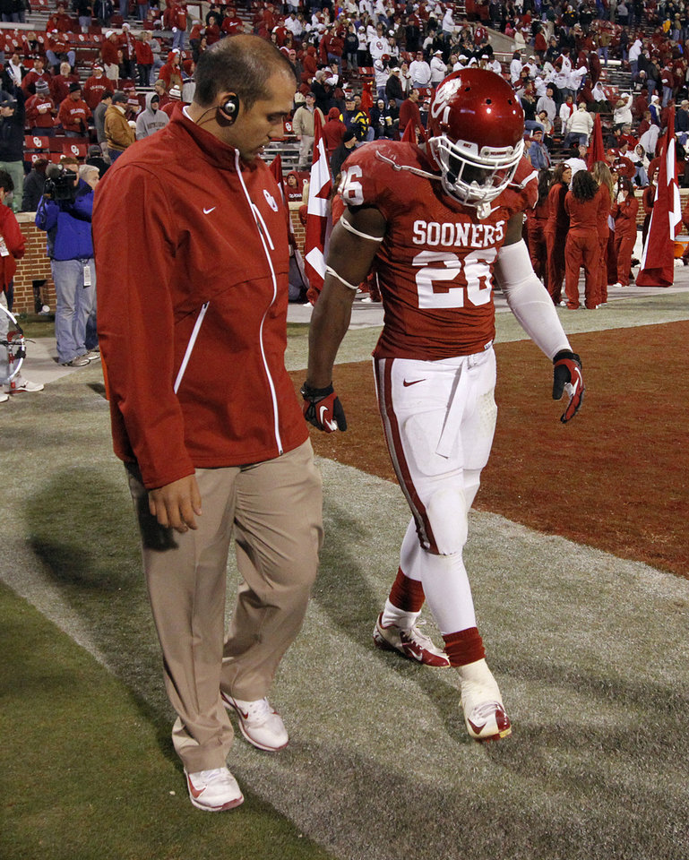 Photo - OU's Damien Williams (26) walks off the field with a trainer after being hurt during the college football game between the University of Oklahoma Sooners (OU) and the Notre Dame Fighting Irish at the Gaylord Family-Oklahoma Memorial Stadium on Saturday, Oct. 27, 2012, in Norman, Okla. Photo by Chris Landsberger, The Oklahoman