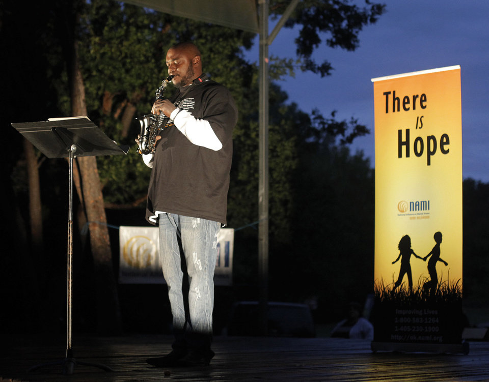 "Moe Williams performs ""Amazing Grace"" on his saxophone in memory of his father and son during the candlelight vigil."