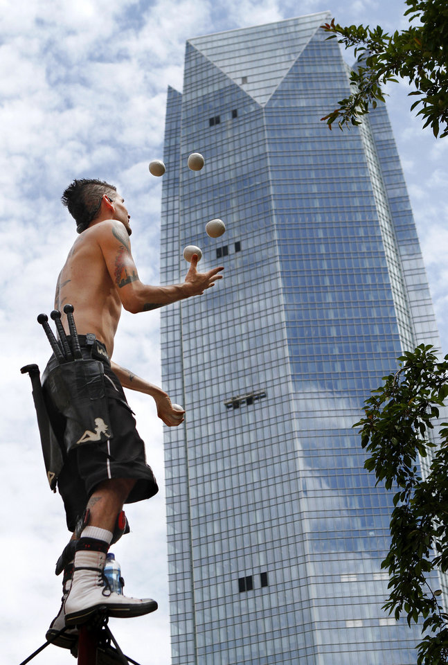 Photo - Above: Comedian, contortionist and daredevil Al Millar juggles Thursday while perched atop a 12-foot pole during one of his three daily Festival of the Arts performances.