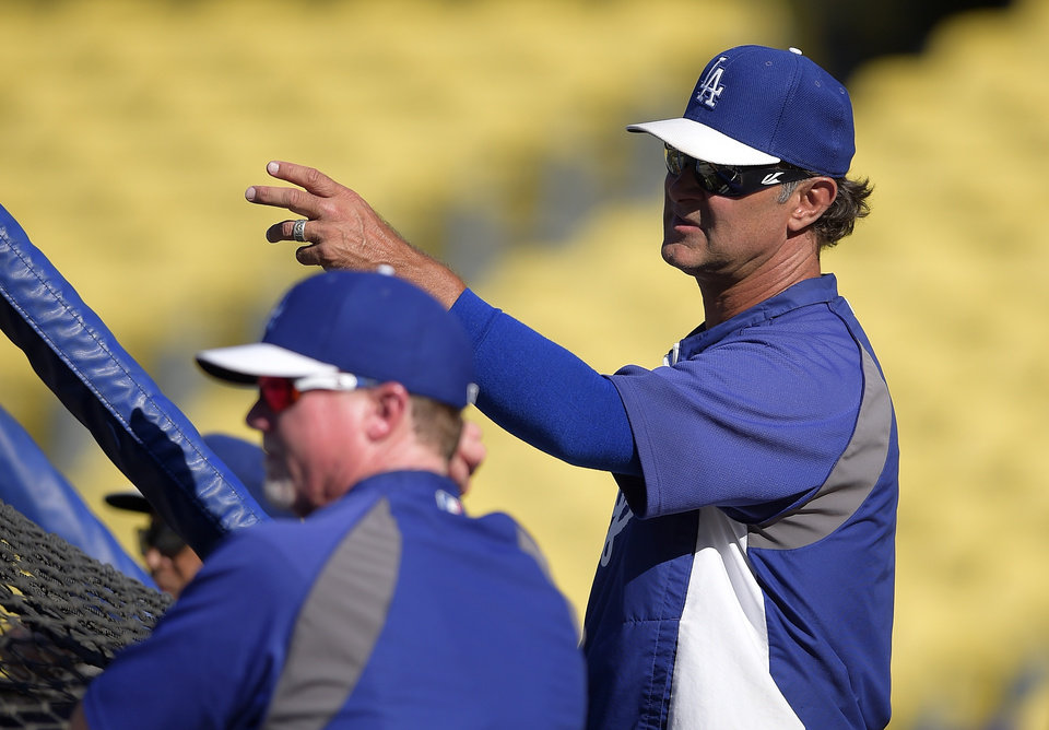 Photo - Los Angeles Dodgers manager Don Mattingly, right, talks with batting coach Mark McGwire during batting practice prior a baseball game against the Atlanta Braves, Thursday, July 31, 2014, in Los Angeles. (AP Photo/Mark J. Terrill)