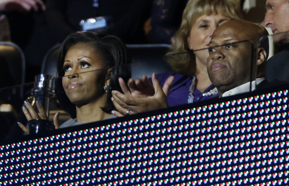 Photo - First lady Michelle Obama and her brother Craig Robinson applaud speakers during the Democratic National Convention in Charlotte, N.C., on Wednesday, Sept. 5, 2012. (AP Photo/Charlie Neibergall)  ORG XMIT: DNC175