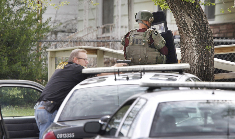 Photo - Oklahoma City Police and FBI agents surround a home at 3024 NE 16th street where three suspects in connection to the robbery of MidFirst Bank were taken into custody in Oklahoma City , Friday April 12, 2013. Photo By Steve Gooch, The Oklahoman