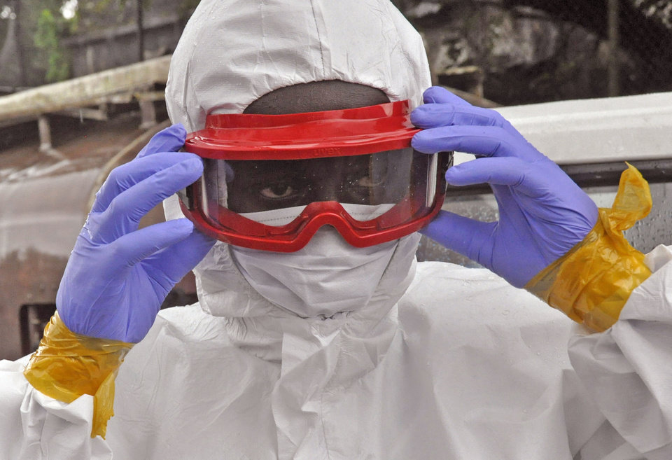 Photo - A Liberian health worker prepare his Ebola protective gear before removing the body of a man that they believe died from the Ebola virus  in Monrovia, Liberia, Friday, Aug. 29, 2014.  The Ebola outbreak in West Africa eventually could exceed 20,000 cases, more than six times as many as are now known, the World Health Organization said Thursday. A new plan released by the U.N. health agency to stop Ebola also assumes that the actual number of cases in many hard-hit areas may be two to four times higher than currently reported.(AP Photo/Abbas Dulleh)