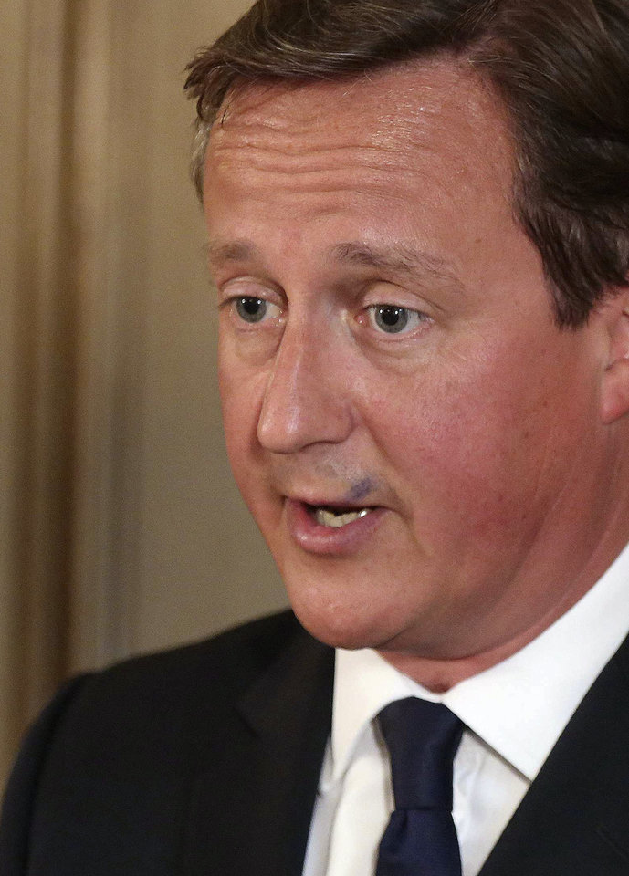 Photo - British Prime Minister David Cameron has a smudge of pen ink on his top lip, as he delivers a report to the media in Downing Street, London, Friday Aug. 29, 2014. Britain's Home Secretary Theresa May has announced that UK's terror threat level is being raised from