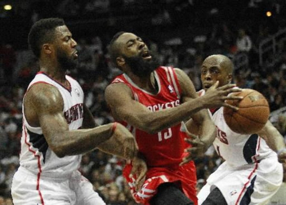 Houston Rockets shooting guard James Harden,center, is fouled as he drives between Atlanta Hawks shooting guard DeShawn Stevenson (92) and Devin HArris, right, in the second half of an NBA basketball game on Friday, Nov. 2, 2012, in Atlanta. Houston won 109-102. (AP Photo/John Bazemore)