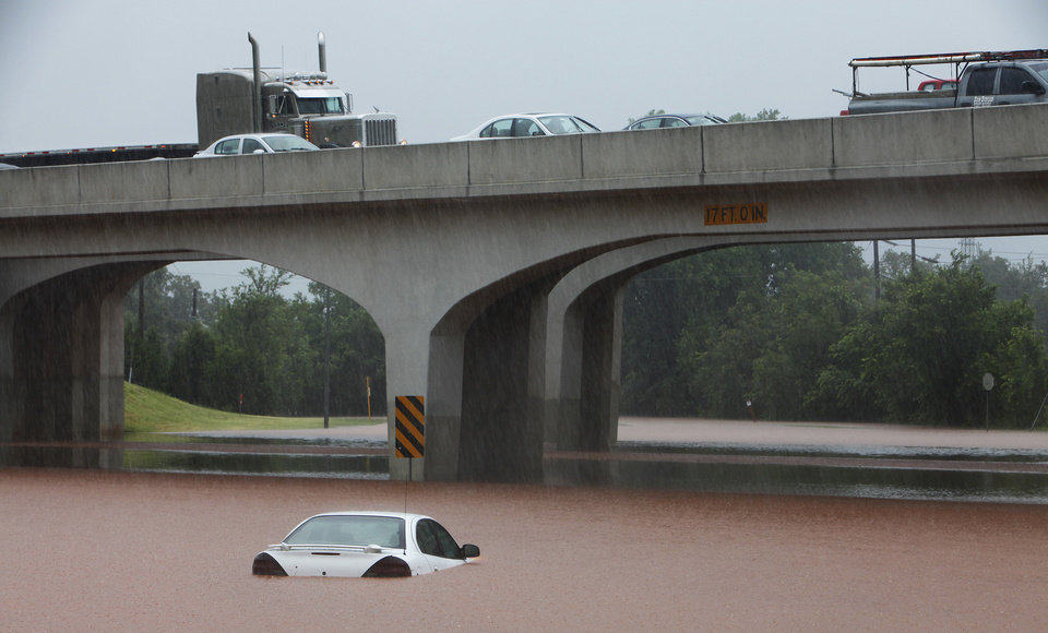 Photo - A car sits in high water on Grand under I-44, Monday,  June 14, 2010.    Photo by David McDaniel, The Oklahoman