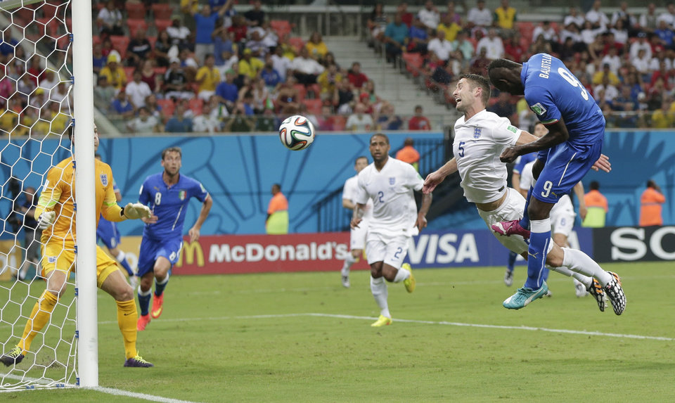 Photo - Italy's Mario Balotelli (9) heads the ball past England's Gary Cahill (5) and goalkeeper Joe Hart, left, to score Italy's second goal during the group D World Cup soccer match between England and Italy at the Arena da Amazonia in Manaus, Brazil, Saturday, June 14, 2014. (AP Photo/Marcio Jose Sanchez)