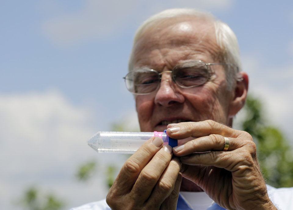 Photo - In this Friday, July 25, 2014 photo, Benny McLean, of Uncle Matt's organic orange juice company, holds up a vial containing the tamarixia wasp which they release in their orange groves in hopes of combating the citrus greening disease, in Clermont, Fla.  Florida's $9 billion citrus industry is facing its biggest threat yet by a tiny invasive bug called the Asian Citrus Psyllid, which carries bacteria that are left behind when the psyllid feeds on a citrus tree's leaves. (AP Photo/Lynne Sladky)
