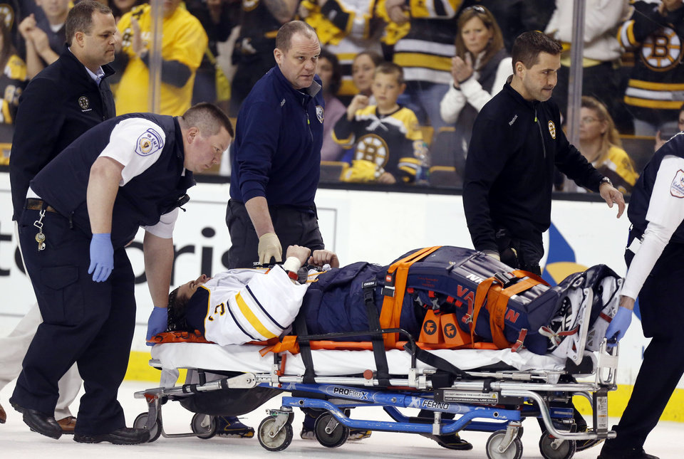 Photo - Buffalo Sabres' Matt Hackett (31) is carted off the ice on a stretcher after getting injured in the third period of an NHL hockey game against the Boston Bruins in Boston, Saturday, April 12, 2014. The Bruins won 4-1. (AP Photo/Michael Dwyer)