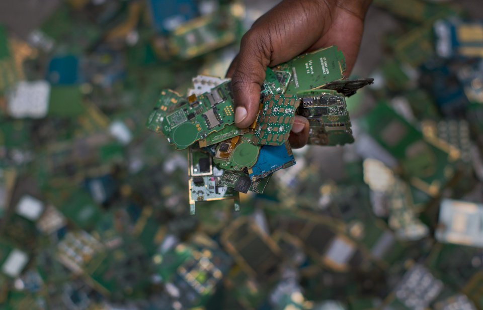 Photo - In this photo taken Monday, Aug. 18, 2014, a worker gathers handfuls of cellphone printed circuit boards from a pile to put in a sack for recycling, at the East African Compliant Recycling facility in Machakos, near Nairobi, in Kenya. The amount of electronic waste generated globally last year is enough to fill 100 Empire State Buildings and represents more than 15 pounds (6.8 kilograms) for every living person, according to the U.N. Environmental Program, with much of that e-waste exported to developing countries like India and Kenya in the form of used goods. (AP Photo/Ben Curtis)
