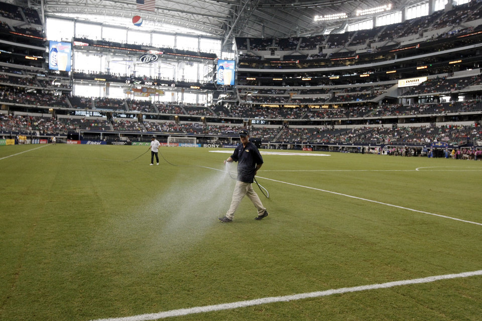 A grounds crew member waters the turf before the Gold Cup semifinals between the United States and Honduras at Cowboys Stadium, Wednesday, July 24, 2013, in Arlington, Texas. (AP Photo/Brandon Wade)