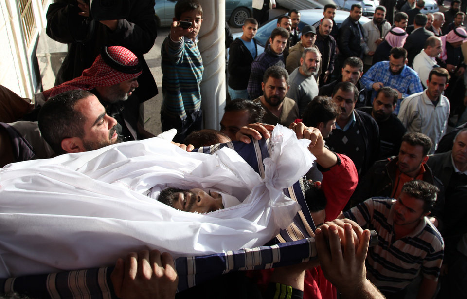 Photo - Syrians and Jordanians carry the body of Moath al-Rawashdy, 30 years, who was killed from Syrian government forces shelling during his funeral procession in Ramtha City, north Amman, Jordan, Sunday, Dec. 2, 2012. Al-Rawashdy was killed in Tafas village, in the Syrian city of Daraa, on Dec. 1, 2012. Syrian refugees, who crossed the border into Jordan last night from Tafas village, in Daraa, tried to rescue him as they smuggled him into Jordan, but he died on the way. (AP Photo/Mohammad Hannon)