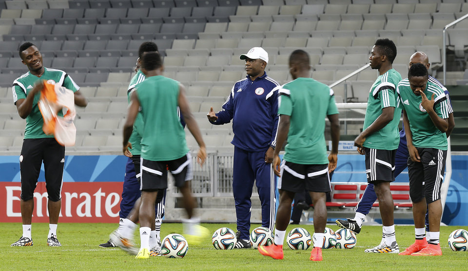 Photo - Nigeria's coach Stephen Keshi gestures to players during an official training session the day before the group F World Cup soccer match between Iran and Nigeria at the Arena da Baixada in Curitiba, Brazil, Sunday, June 15, 2014.  (AP Photo/Frank Augstein)