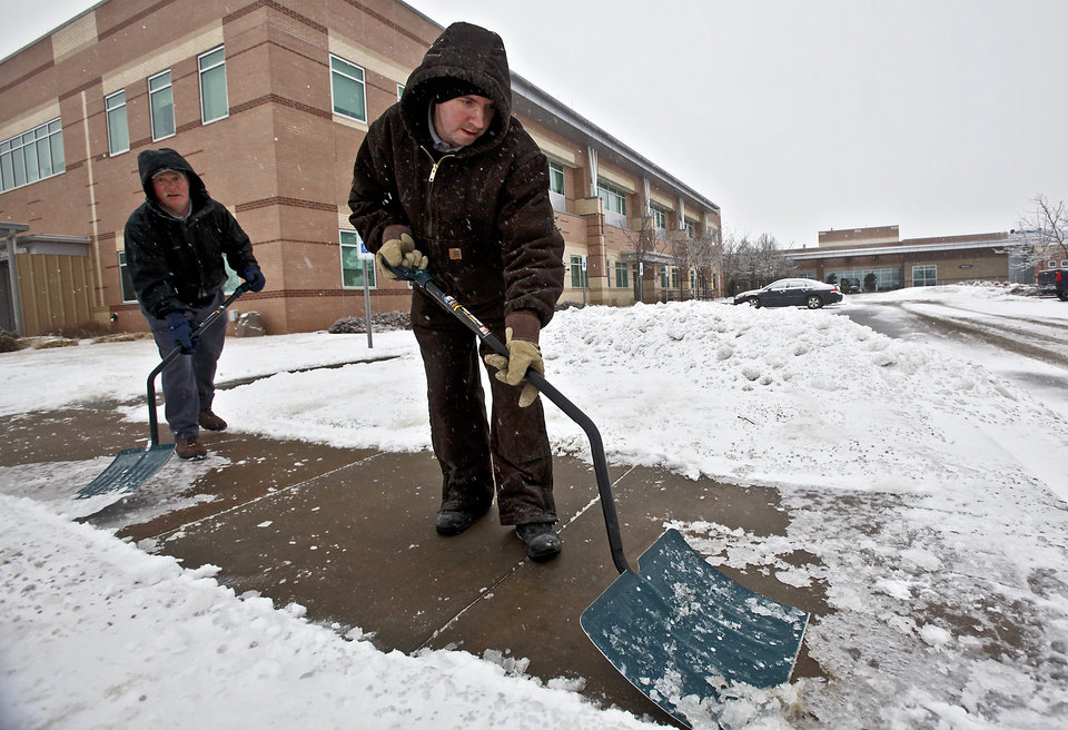 Photo - John Robbins, left, and John McBride uses a snow shovel to clear the sidewalks and parking lots of ice and snow at Integris Canadian Valley Hospital on Friday, Jan. 29, 2010, in Yukon, Okla.   Photo by Chris Landsberger, The Oklahoman