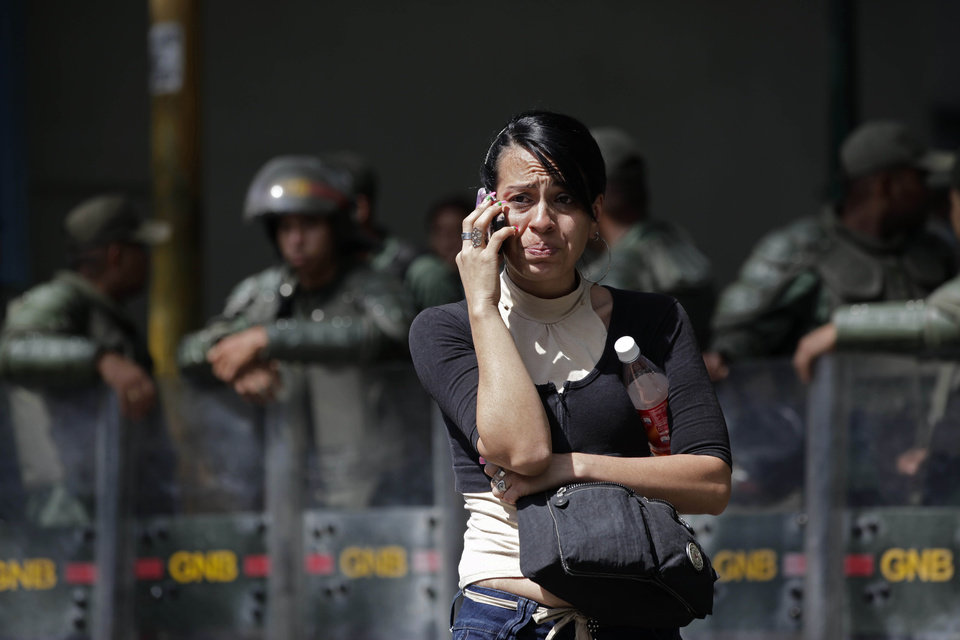 Photo -   An inmate's relative cries as she uses a cell phone outside La Planta prison where National Guard soldiers stand behind in Caracas, Venezuela, Saturday, April 28, 2012. Hundreds of inmate's relatives were not allowed to enter for normal visiting hours because they were canceled after authorities foiled plans for a prison break on Friday. Venezuelan authorities say they discovered a tunnel that inmates had dug leading to a sewer. (AP Photo/Ariana Cubillos)