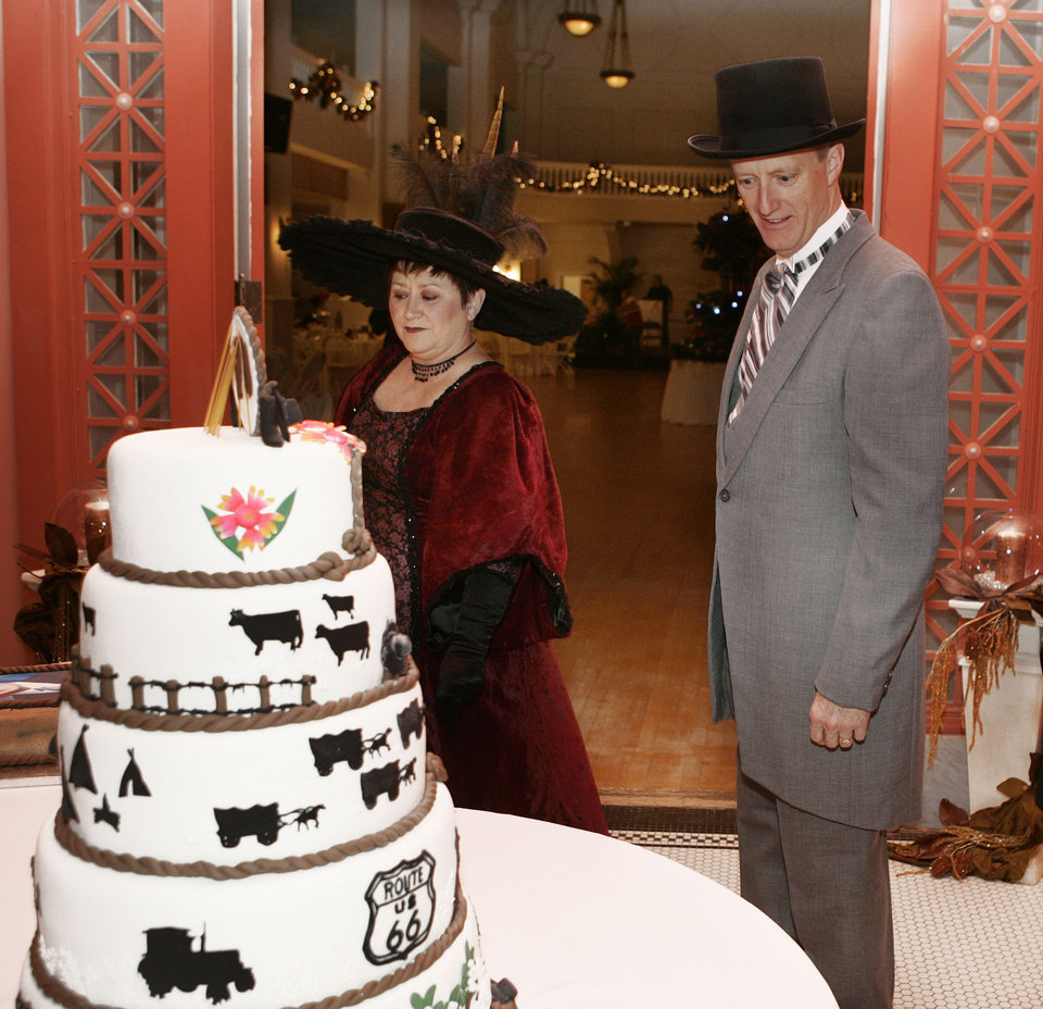 Photo - Joy and Dan Newton of Guthrie, look over the Oklahoma Centennial birthday cake as they arrive in 1900's-period dress for the Oklahoma Centennial Statehood Inaugural Ball, Saturday, Nov. 17, 2007, at the Guthrie Scottish Rite Masonic Center, in Guthrie, Okla. By Bill Waugh, The Oklahoman