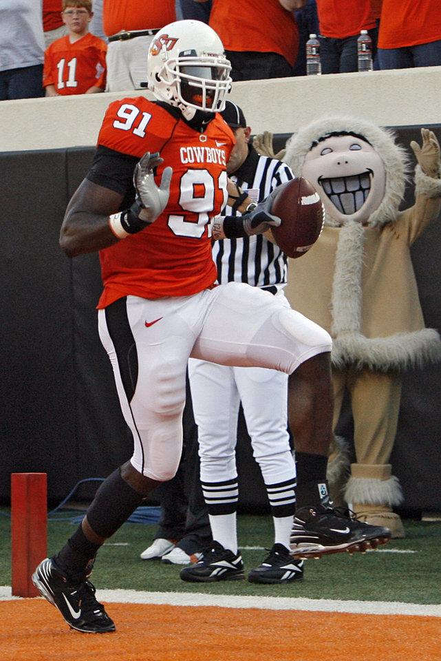 Photo - Oklahoma State's Ugo Chinasa (91) runs the ball into the end zone on an interception return during the first half of the college football game between the Oklahoma State University Cowboys (OSU) and the Texas A&M University Aggies (TAM) at Boone Pickens Stadium on Saturday, Oct. 4, 2008, in Stillwater, Okla.  CHRIS LANDSBERGER, THE OKLAHOMAN  ORG XMIT: KOD