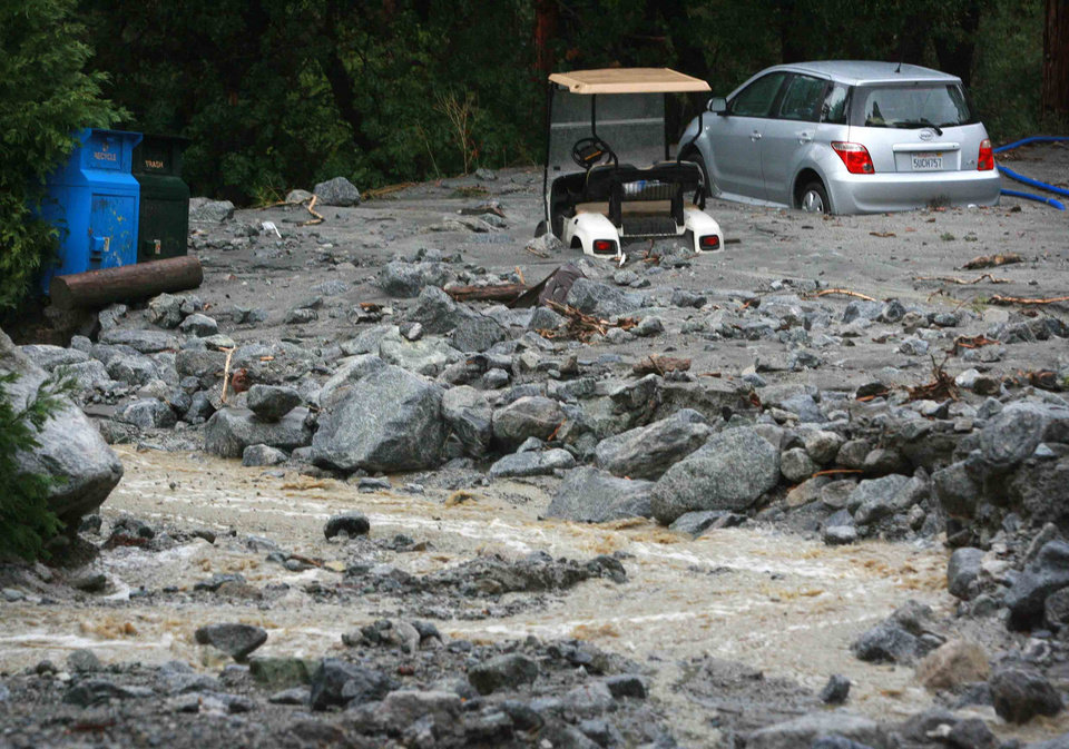 Photo - In this Sunday, Aug. 3, 2014 photo, a golf cart and passenger vehicle are partially buried at Forest Home Christian Conference Center in Forest Falls, Calif. following a rock and mudslide. Crews on Monday have cleared several feet of mud, rocks and debris that had blocked San Bernardino County roads, stranding some 2,500 people in the rural communities of Oak Glen and Forest Falls. (AP Photo/The Press-Enterprise, David Bauman)  MAGS OUT; MANDATORY CREDIT