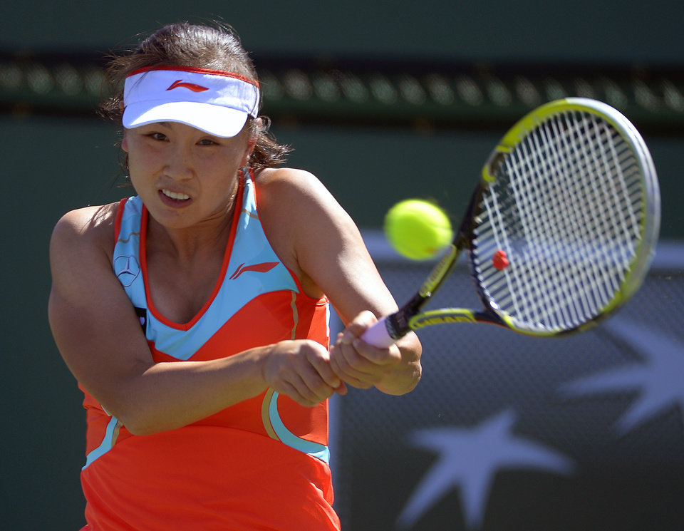 Photo - Peng Shuai, of China, returns a shot against Samantha Stosur, of Australia, during their match at the BNP Paribas Open tennis tournament, Monday, March 11, 2013, in Indian Wells, Calif. (AP Photo/Mark J. Terrill)