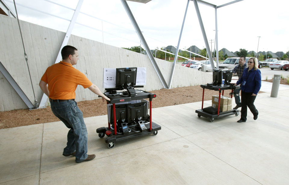 IT Tech's Matt Cotter (front), Pam Buchanan, and Steven Isaacs move computer equipment into the new Northwest Library in Oklahoma City, OK, Monday, April 30, 2012,  By Paul Hellstern, The Oklahoman