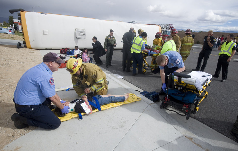 San Bernardino County Fire Department paramedics and AMR EMT's treat one of the victims from an over turned school bus on Nisqualli Road in Victorville Calif. Thursday October 11, 2012. A school bus carrying 40 children in Southern California has been knocked on its side in a crash that has injured 13 children and the bus driver. (AP Photo/The Victor Valley Daily Press, James Quigg)