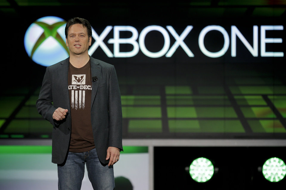 Photo - FILE - In this June 10, 2013 file photo, Phil Spencer of Microsoft Game Studios speaks at the Microsoft Xbox E3 media briefing in Los AngelesWith the launch of the Xbox One, PlayStation 4 and Wii U in the video game industry's rearview mirror, the spotlight at the Electronic Entertainment Expo, held June 10-12, 2014, is expected to shift back to games. From online-only titles to virtual reality experiences, about 200 exhibitors will  hype their latest software in hopes of driving away from E3 with The Next Big Thing. (AP Photo/Jae C. Hong, file)