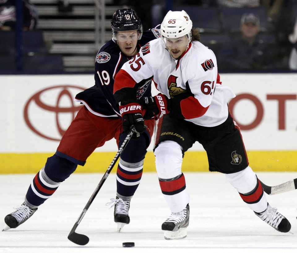 Photo - Ottawa Senators' Erik Karlsson, right, of Sweden reaches for the puck against Columbus Blue Jackets' Ryan Johansen  in the first period of an NHL hockey game in Columbus, Ohio, Tuesday, Nov. 5, 2013. (AP Photo/Paul Vernon)