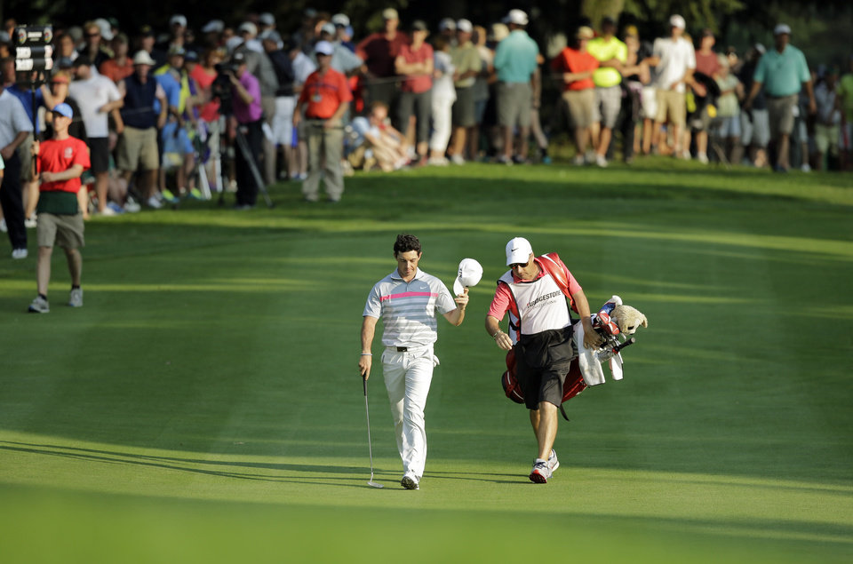Photo - Rory McIlroy tips his hat as he walks down the 18th fairway with caddie J.P. Fitzgerald during the final round of the Bridgestone Invitational golf tournament Sunday, Aug. 3, 2014, at Firestone Country Club in Akron, Ohio. McIlroy's 15-under par total beat Sergio Garcia by two shots. (AP Photo/Mark Duncan)