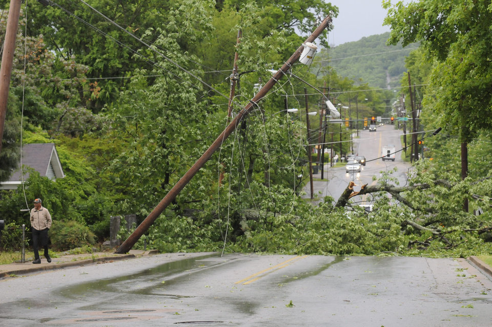 Photo - A felled power pole and street light blocks the 1300 block of N. Chamberlain Ave. Wednesday morning in Trenton, Ga., as Eddie Dancy, left, surveys the storm damage to his neighborhood.   (AP Photo/Chattagooga Times Free Press, Tim Barber)