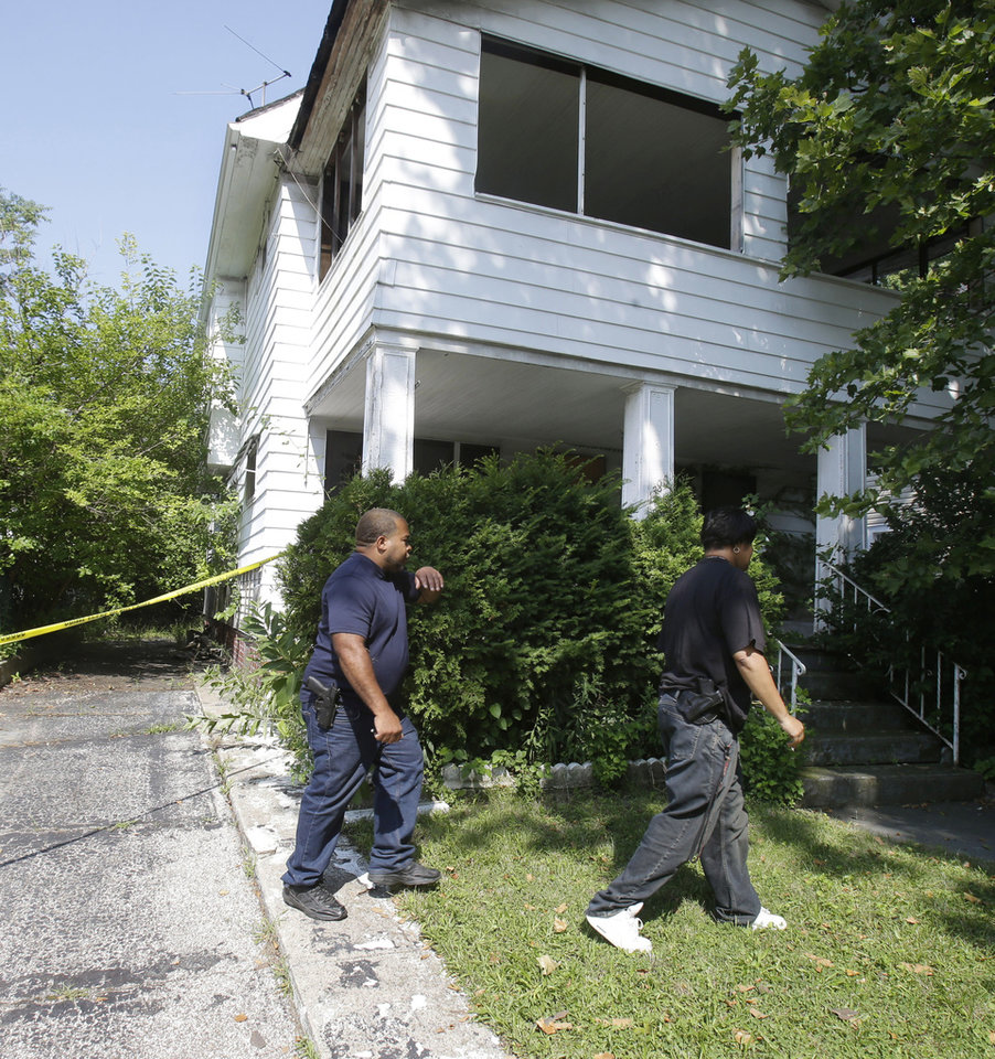 East Cleveland police search a house Sunday, July 21, 2013, where a body was recently found  in East Cleveland, Ohio. The bodies, believed to be female, were found about 100 to 200 yards (90 to 180 meters) apart, and a 35-year-old man was arrested and is a suspect in all three deaths, though he has not yet been charged, East Cleveland Mayor Gary Norton said Saturday. (AP Photo/Tony Dejak)