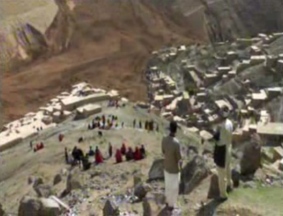 Photo - This image made from AP video shows people searching for survivors after a massive landslide landslide buried a village Friday, May 2, 2014 in Badakhshan province, northeastern Afghanistan, which Afghan and U.N. officials say left hundreds of dead and missing missing. (AP Photo via AP video)