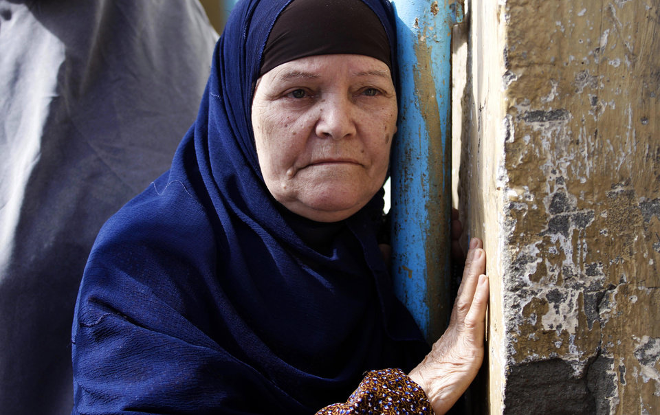 An Egyptian elderly woman rests on the wall as she waits in a line outside a polling station to cast her vote during the first day of the presidential election in Alexandria, Egypt, Wednesday, May 23, 2012. More than 15 months after autocratic leader Hosni Mubarak's ouster, Egyptians streamed to polling stations Wednesday to freely choose a president for the first time in generations. Waiting hours in line, some debated to the last minute over their vote in a historic election pitting old regime figures against ascending Islamists.(AP Photo/Khalil Hamra) ORG XMIT: KH104