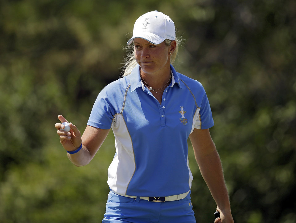 Photo - Europe's Suzann Pettersen, from Norway, waves to the crowd after parring the second hole during her singles match against United States' Lizette Salas at the Solheim Cup golf tournament on Sunday, Aug. 18, 2013, in Parker, Colo. (AP Photo/Chris Carlson)