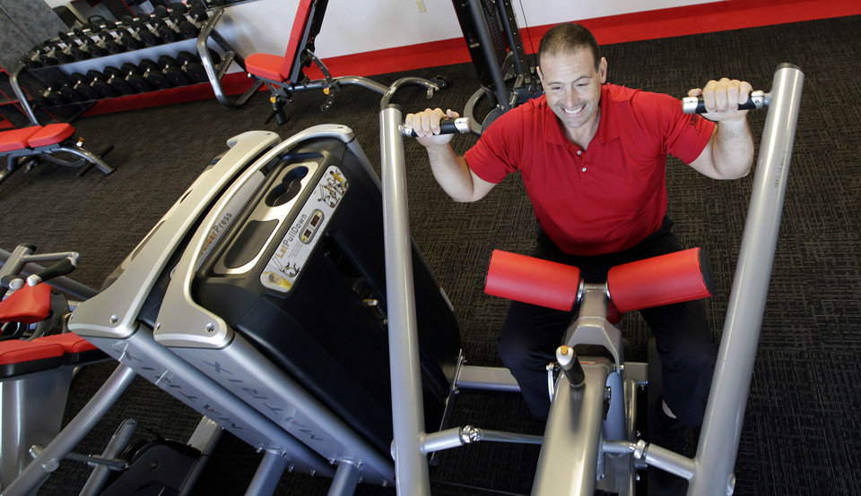 Photo -   ADDS FULL NAME OF GYM - In this June 14, 2012, photo, gym manager Rick Limitone demonstrates a work out machine at Snap Fitness Rolling Strong Gym. a truck stop gym in Dallas. From trucking companies embracing wellness and weight-loss programs to gyms being installed at truck stops, momentum has picked up in recent years to help those who make their living driving big rigs get into shape. (AP Photo/LM Otero)