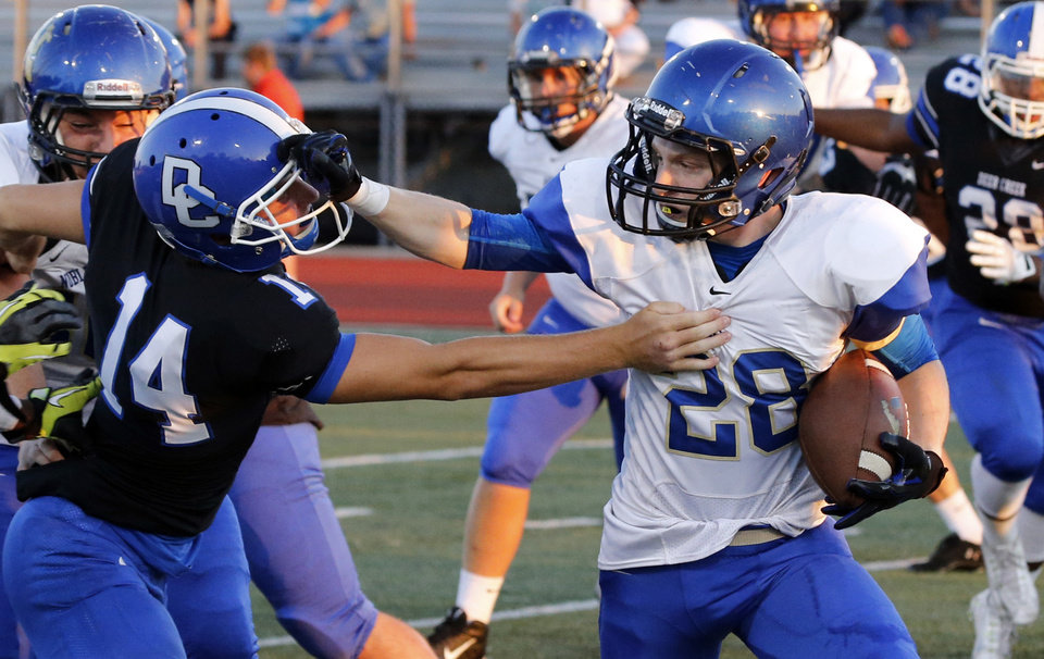 Photo - Noble's Tyler Showers tries to shed a tackle by Deer Creek's Jacob Schimmels carries in the Top of the World scrimmage at Harve Collins Field in Norman, Okla., on Friday, Aug. 29, 2014. Photo by Steve Sisney, The Oklahoman