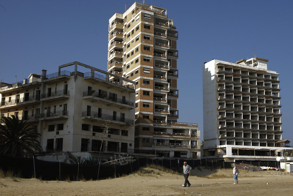 Photo - A couple walk on the beach by the deserted hotels in an area used by the Turkish military in the Turkish occupied area in the abandoned coastal city of Varosha, in Famagusta, in southeast of island of Cyprus, Friday, Jan. 17, 2014. Time virtually stopped in 1974 for the Mediterranean tourist playground of Varosha. When Turkey invaded Cyprus in the wake of a coup by supporters of union with Greece, thousands of residents fled, and chain-link fences enclosed a glamorous resort that it's said once played host to Hollywood royalty like Elizabeth Taylor. The town's crumbling, war-scarred beachfront hotels have become an emblem of the country's division between Turks and Greeks. In 40 years, few have set foot inside the town, which remains heavily guarded by the Turkish army and twists of barbed wire. But that grim scene could present a rare opportunity. Massachusetts Institute of Technology architecture professor Jan Wampler calls it the greatest challenge of his career: he and a team of architects, urban planners, business leaders and peace activists hope to rebuild an entire town to correct past errors and mold a sustainable, ecological habitat. (AP Photo/Petros Karadjias)