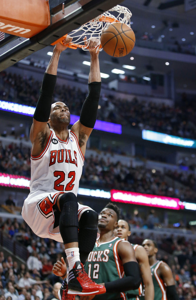 Photo - Chicago Bulls forward Taj Gibson, left, scores in front of Milwaukee Bucks guard Jeff Adrien during the first half of an NBA basketball game in Chicago, Friday, April 4, 2014. (AP Photo/Kamil Krzaczynski)