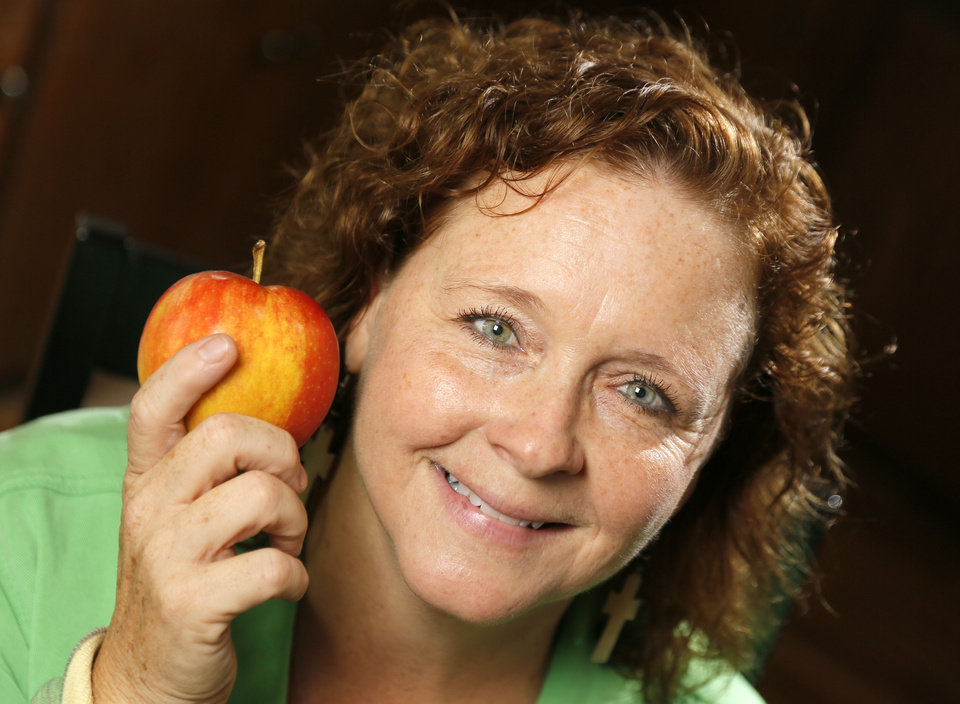 Photo - Sharon Allen, founder of Apples for Africa, holds an apple in the kitchen of her Piedmont home.   NATE BILLINGS - NATE BILLINGS