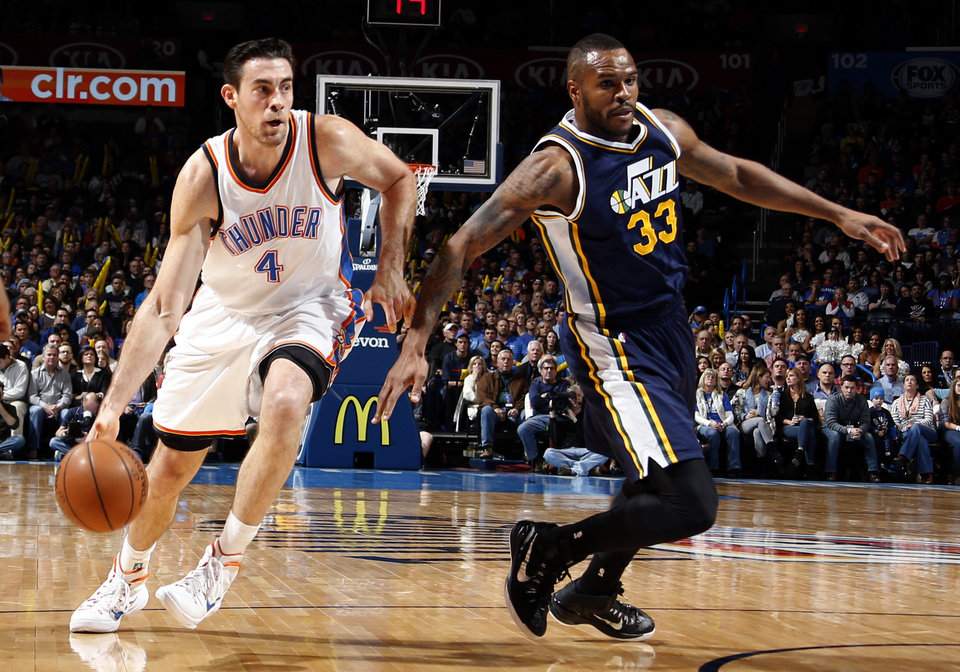Photo - Oklahoma City's Nick Collison (4) drives past Utah's Trevor Booker (33) during the NBA basketball game between the Oklahoma City Thunder and the Utah Jazz at the Chesapeake Energy Arena in Oklahoma City, Friday, Jan. 9, 2015. Photo by Sarah Phipps, The Oklahoman