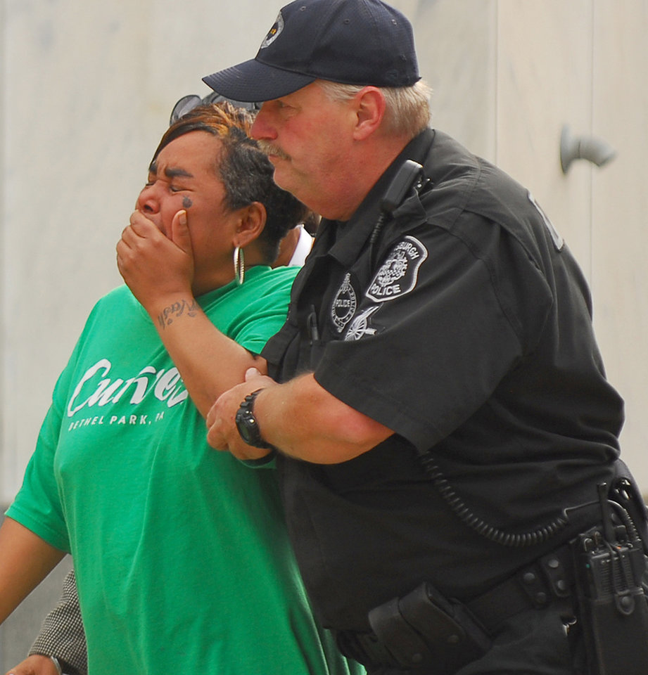 Photo -   Ronda Thaxton, the mother of Klein Michael Thaxton is escorted by Pittsburgh Police Officer Ray Kain to the command center during the standoff atThree Gateway Center, Friday, Sept. 21, 2012. Klein Michael Thaxton, 22, held a businessman hostage inside the office building for more than five hours Friday, posting Facebook updates during the standoff, and surrendered to authorities without incident, police said. (AP Photo/The Tribune-Review, Keith Hodan) PITTSBURGH OUT