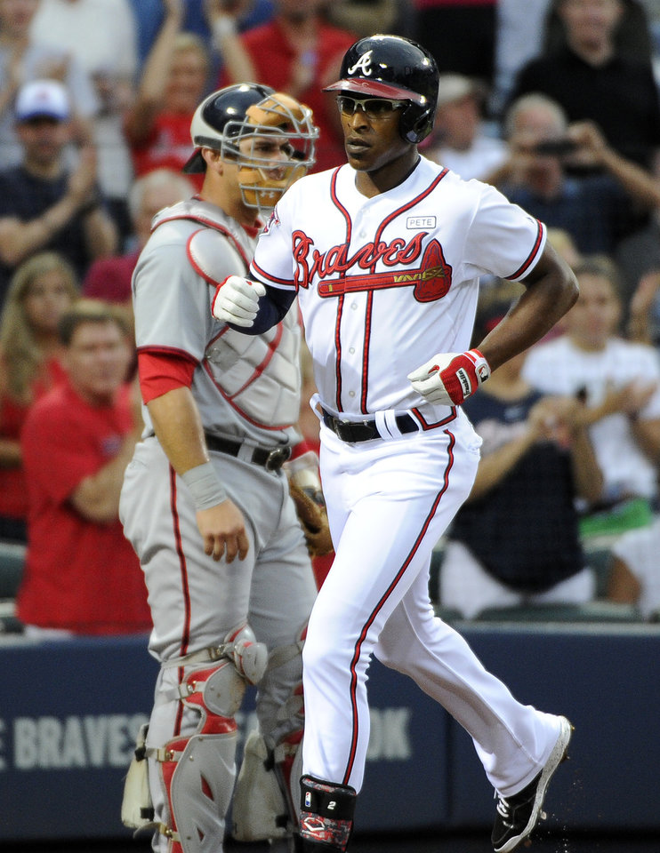 Photo - Atlanta Braves' B.J. Upton, right, scores in front of Washington Nationals catcher Wilson Ramos on his two-run home run during the second inning of a baseball game Friday, Aug. 8, 2014, in Atlanta. (AP Photo/David Tulis)