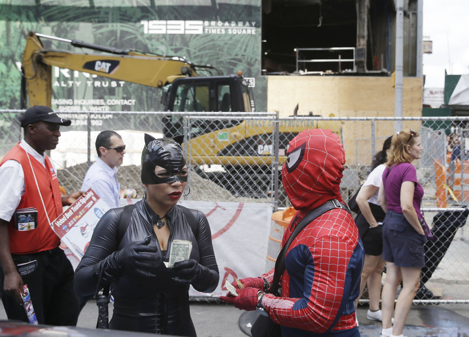 "Photo - People dressed as Catwoman, left, and Spiderman split tips after taking a picture with some tourists in Times Square on Monday, July 28, 2014 in New York.  New York City Mayor Bill de Blasio said Monday that he believes the people wearing character costumes in Times Square should be licensed and regulated. Dozens of people dressed as kids' favorites like Elmo, Cookie Monster and Batman stand near 42nd Street and pose for photos with tourists in exchange for money. De Blasio said the practice has ""gone too far.""  A man dressed as Spider-man was arrested Saturday, July 28, 2014, after punching a police officer who told him to stop harassing tourists.  The City Council is working on legislation that would require the characters to get a city-approved license.  (AP Photo/Seth Wenig)"